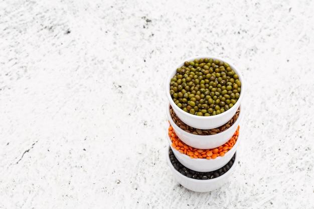 Verschiedene zusammenstellung von indischen hülsenfrüchten in weißen melaminschalen auf weißem hintergrund mit copyspace.