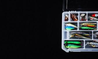 Verschiedener bunter Fischereiköderkasten auf schwarzem Hintergrund