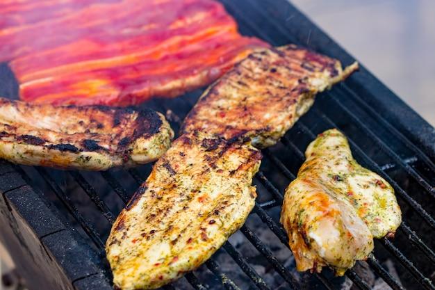 Verschiedener gemischter grill aus hühnerfleisch und schweinefleisch, würstchen, die auf grillrost gebraten werden, zubereitet für ein sommerliches familienessen.