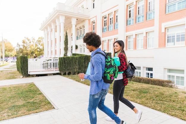 Verschiedener jugendpaarstudent, der zusammen außerhalb des hochschulgebäudes geht