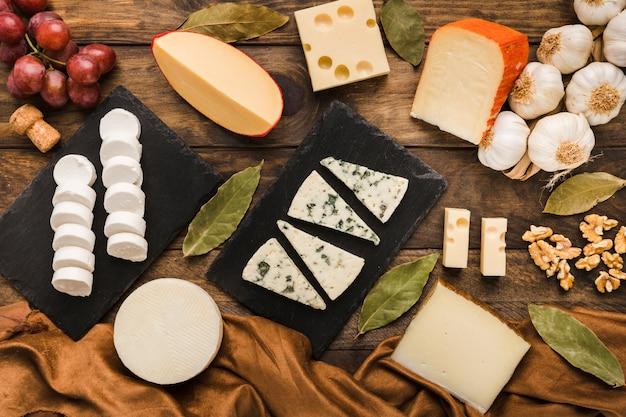 Verschiedener käse und bestandteil auf hölzernem schreibtisch