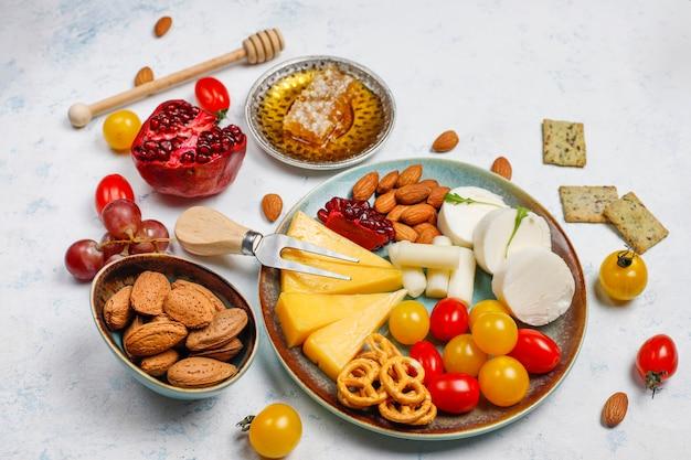 Verschiedener käse und käseplatte auf leuchtpult mit verschiedenen nüssen und früchten