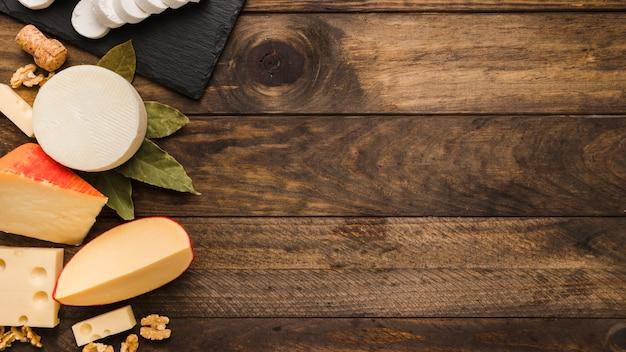 Verschiedener köstlicher käse mit lorbeerblättern und walnuss auf hölzernem strukturiertem