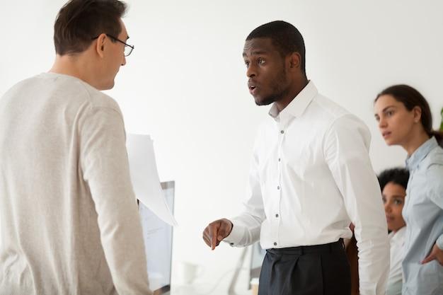 Verschiedener schwarzer angestellter und weißer chef, die bei der arbeit argumentieren
