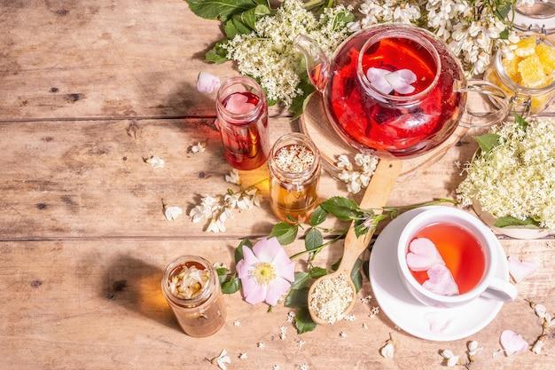 Verschiedener tee aus blumen. frischer holunder, hagebutte und akazie. gesundes lebensmittelkonzept. alte holzbretter hintergrund, ansicht von oben