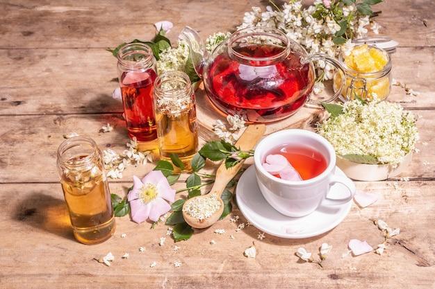 Verschiedener tee aus blumen. frischer holunder, hagebutte und akazie. gesundes lebensmittelkonzept. alte holzbretter hintergrund, kopienraum