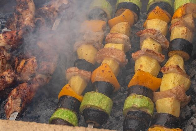 Verschiedenes fleisch von hühnchen und schwein und verschiedenes gemüse auf dem grill für das sommerliche familienessen