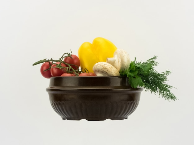 Verschiedenes frisches gemüse in keramikschale auf weißem hintergrund in horizontaler perspektive