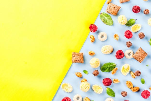 Verschiedenes frühstückskost aus getreide, himbeeren und minze auf blauem gelb