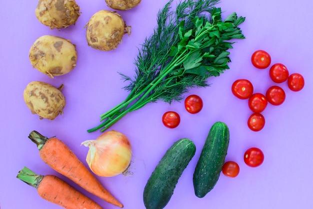 Verschiedenes gemüse auf violettem hintergrund, gemüse - kartoffeln, karotten, zwiebeln, tomaten, gurken und grüns. gesunde ernährung.