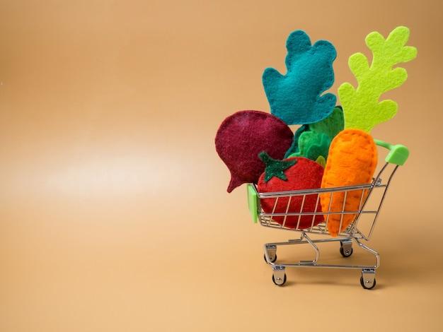 Verschiedenes gemüse in einem einkaufswagen aus einem supermarkt auf orangefarbenem hintergrund, gemüse aus filz