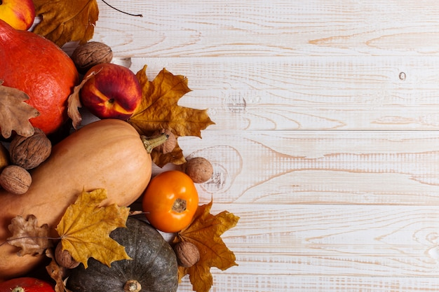 Verschiedenes gemüse, kürbise, äpfel, birnen, nüsse, tomaten und trockene blätter auf einem weißen hölzernen hintergrund. herbststimmung, copyspace. ernte .