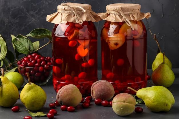 Verschiedenes hartriegelkompott mit pfirsichen und birnen in gläsern