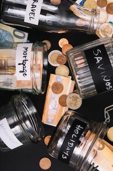 Verschiedenes offenes glas mit eurobargeldanmerkung und -münzen auf schwarzem hintergrund