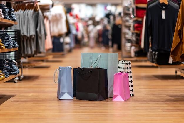 Verschiedenfarbige taschen unterschiedlicher größe befinden sich auf einem haufen in der mitte des handelsbereichs des geschäfts.