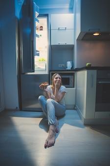 Verschlafene frau, die spät in der nacht am offenen kühlschrank auf dem boden sitzt