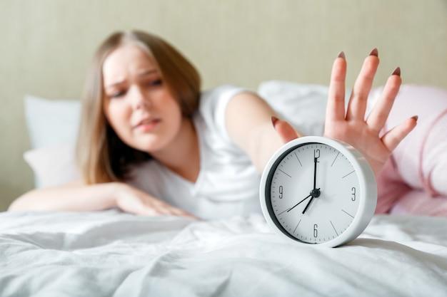 Verschlafene junge frau, die im schlafanzug wach ist, schaltet den wecker in eile aus. morgenroutine und spätes aufwachen vom wecker im bett. frau ist spät in panik nach schlaflosigkeit schlaflosigkeit. ungesunder schlaf.