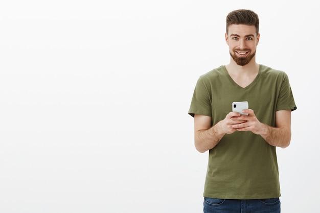 Verschlagener und aufgeregter gut aussehender reifer bärtiger mann im olivgrünen t-shirt, der smartphone hält und erfreut grinst, als interessante idee des nächsten beitrags online über weiße wand