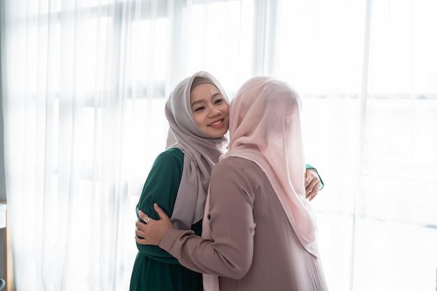 Verschleierte frau umarmt und küsst ihre schwester beim treffen