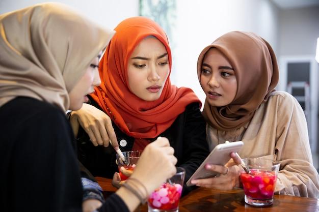 Verschleierte junge frau, die sich mit smartphone für das ansehen des videos entspannt und nach dem anschauen schockiert