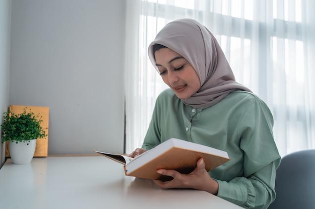 Verschleierte junge frau hält das heilige buch des korans