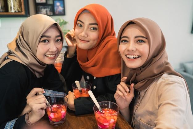Verschleierte junge frauen betrachten kamera entspannend mit smartphone für selfie