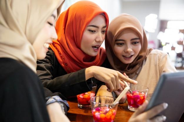 Verschleierte junge frauen, die sich mit chat und scherz mit digitalem tablet entspannen