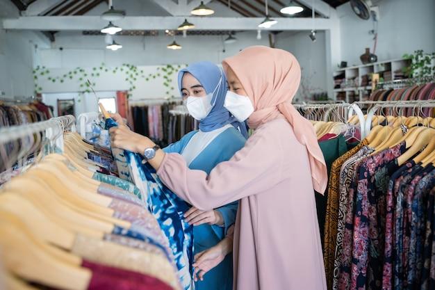 Verschleierte kellnerinnen bedienen weibliche käufer, während sie kleidung auf dem kleiderbügel halten
