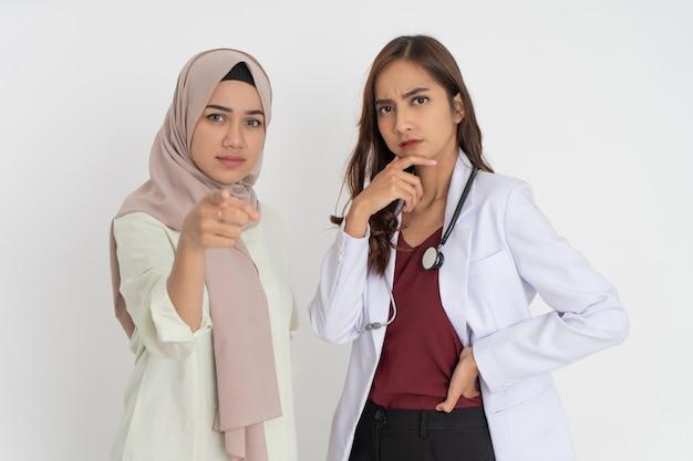Verschleierte patientin mit zeigegeste und schöner ärztin in weißer uniform, die kinn mit ...