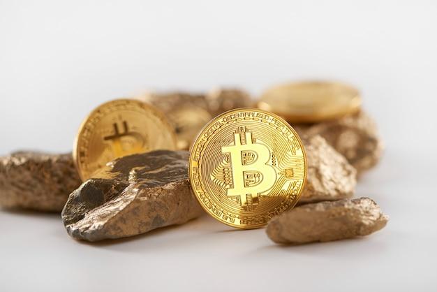 Verschlüsselte goldene bitcoins, die zusammen mit den goldklumpen liegen, die die wichtigsten finanzierungstrends sind, die heutzutage auf weißem hintergrund lokalisiert werden.
