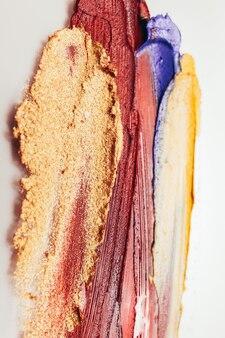 Verschmierter lippenstift. professioneller schönheitssalon. gelbe blaue rote striche auf weißem hintergrund.