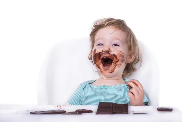 Verschmiertes baby, das schokolade isst