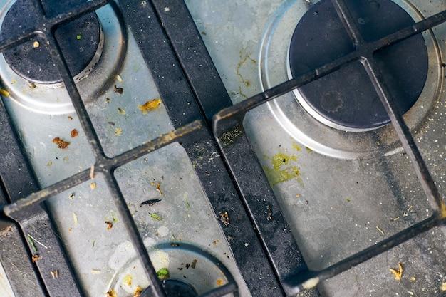 Verschmutzte herdplatte mit ölspritzern, fettflecken und essensresten. unsauberes küchenkochfeld aus stahl mit fettflecken. frühjahrsputz, beseitigung alter küchenflecken, bratflecken, krümel und angebranntes