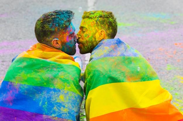 Verschmutzung in homosexuellem paarküssen der farbe eingewickelt in der regenbogenflagge auf lgbt-stolzparade