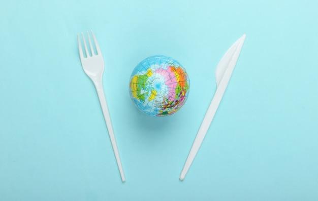 Verschmutzung .kunststofffrei. öko-konzept. globus, plastikmesser mit gabel auf blauem hintergrund. rette den planeten. draufsicht. minimalismus