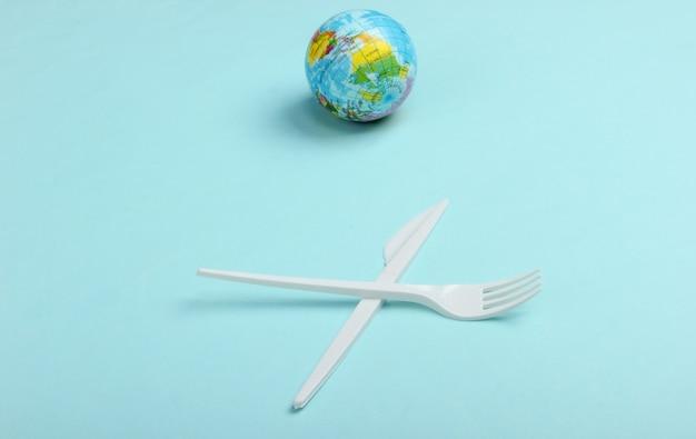 Verschmutzung .kunststofffrei. öko-konzept. plastikmesser mit gabel und globus auf blauem hintergrund. rette den planeten. minimalismus