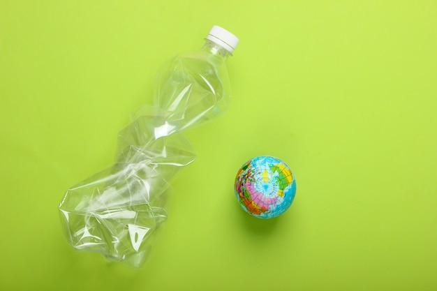 Verschmutzung. plastik frei. öko-konzept. zerknitterte plastikflasche und globus auf grünem hintergrund. draufsicht. minimalismus