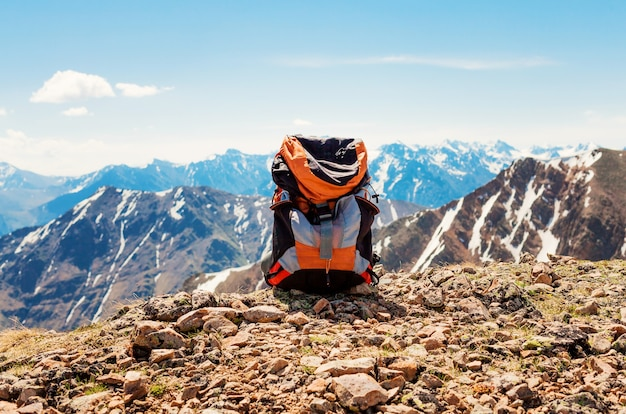 Verschneite berglandschaft. der rucksack des touristen steht auf den felsen an der spitze der berge.