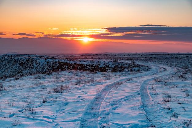 Verschneite landschaft mit straße am sonnenuntergang