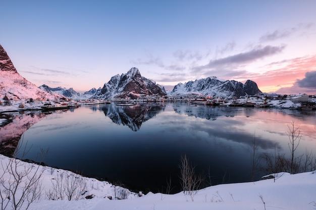 Verschneites skandinavisches dorf mit umgebenem berg an der küste
