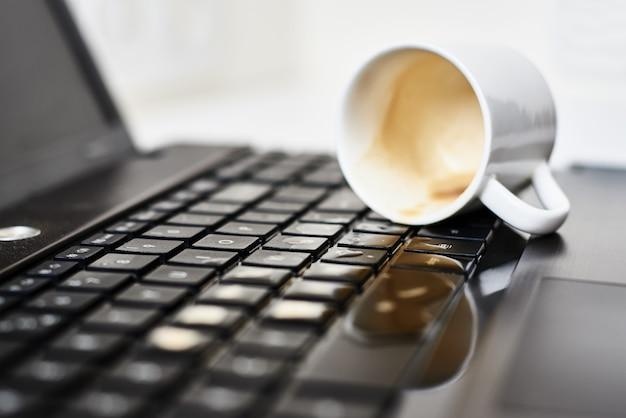 Verschütten sie kaffee aus der weißen tasse auf der tastatur des computer-laptops. beschädigung des computers durch verschüttete flüssigkeit