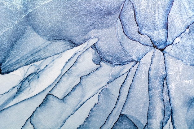 Verschüttete blaue und silberne acrylfarbe. alkoholtinte spritzen
