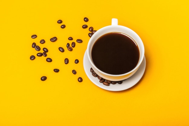 Verschüttete kaffeebohnen auf einem hellen gelben hintergrund