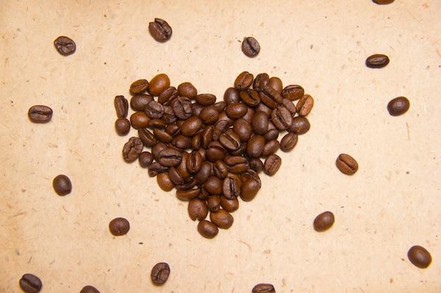 Verschüttete kaffeebohnen. kaffee in form von herzen. geschenkpapier