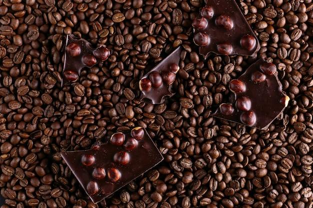 Verschüttete kaffeebohnen und schwarze schokolade, köstlicher hintergrund.