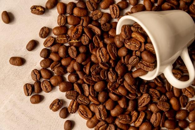 Verschüttete kaffeetasse mit gerösteten bohnen