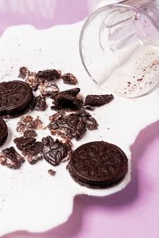 Verschüttete milch mit hoher ansicht der zertrümmerten kekse