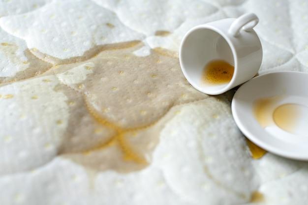 Verschüttete tasse tee auf dem bett. versehentlich fallengelassene tasse mit untertasse auf weißem bettlaken