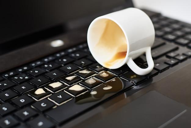 Verschütteter kaffee aus einer weißen tasse auf der computertastatur