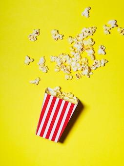 Verschütteter kasten popcorn auf gelbem hintergrund